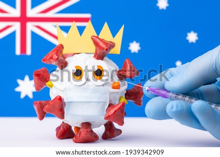 Coronavirus vaccination in Australia. Medical worker making injection to a cartoon Covid-19 model in a protective medical mask in front of flag of Australia