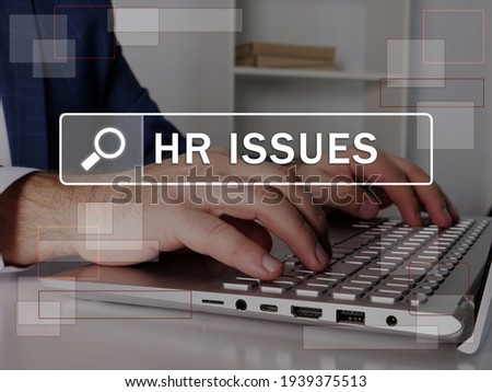 HR ISSUES Human resources text in search line. Modern Banker looking for something at computer. HR ISSUES Human resources concept.  Royalty-Free Stock Photo #1939375513