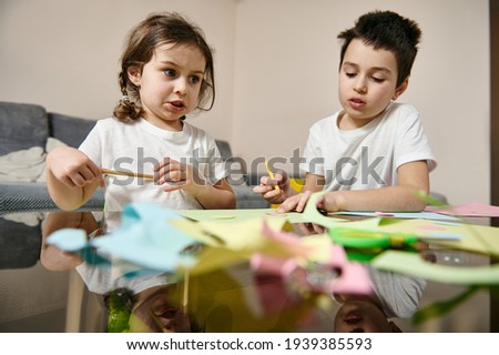 Beautiful school boy and preschool girl draw during art creativity class. Girl expresses sadness and anger