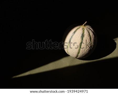 A sunbeam falls on a melon on the table. Dark photo