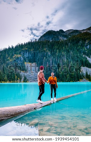 Majestic mountain lake in Canada. Upper Joffre Lake Trail View, couple visit Joffre Lakes Provincial Park - Middle Lake. British Columbia Canada, couple men and woman hiking by the lake Royalty-Free Stock Photo #1939454101
