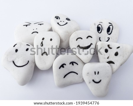 Emotion management concept, stones with painted faces symbolize different emotions. We are all different, but all together, learning to manage emotions. Soft background, white stones. Royalty-Free Stock Photo #1939454776