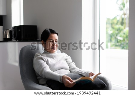 Elderly asian woman reading a book at home,Relax time,Senior lifestyle concept,Long sighted Royalty-Free Stock Photo #1939492441