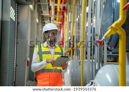 Engineer checking the industry cooling tower air conditioner is water cooling tower air chiller HVAC at large industry factory. Royalty-Free Stock Photo #1939503376