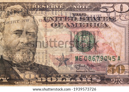 Detail of a 50 US dollar bill with a backlit portrait of President Willis Grant with visible backsplash and watermarks