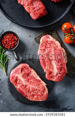 Raw top blade oyster Steak on stone and meat butcher cleaver, marbled beef with herbs tomatoes peppercorns over grey stone surface background top view vertical. Royalty-Free Stock Photo #1939583581