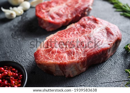 Raw top blade flat Ironcut, on black slate , bio marbled beef with herbs tomatoes peppercorns over grey stone surface background side close up . Royalty-Free Stock Photo #1939583638