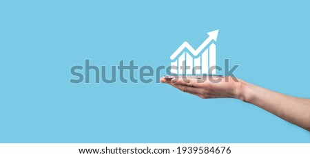Male hand holding smart mobile phone with graph icon.checking analyzing sales data growth graph chart and stock market on global networking. Business strategy, planning and digital marketing.