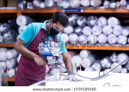 Young man in a face mask and protective chain gloves at work. Man with cutter machine and personal protective equipment at garment industrial work place. Fabric cutter in Asian textile garment factory Royalty-Free Stock Photo #1939589680