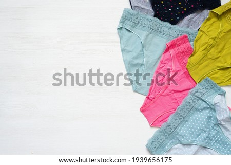 Various colorful cotton women panties on the white wooden table flat lay background.