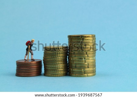 small hiking character and a stack of coins