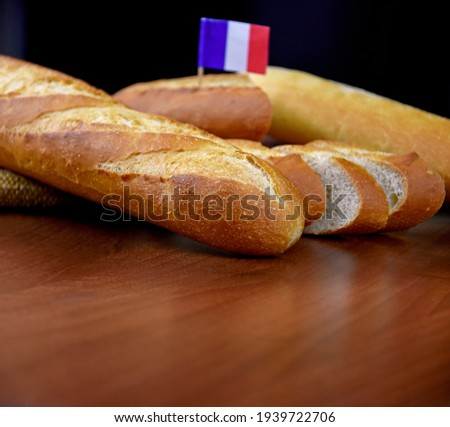 French baguettes on the table brown frame stock images. Pile of french bread with french flag still life stock photo. Fresh baguettes on a wooden background with copy space for text