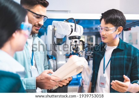Meeting asian Engineers Maintenance Robot Arm at Lab. they are in a High Tech Research Laboratory with Modern Equipment.Professional Japanese Development Engineer is Testing an Artificial Intelligent. Royalty-Free Stock Photo #1939753018