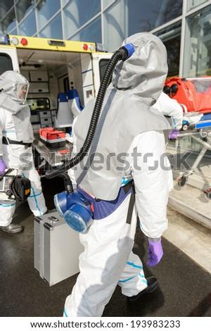 Hazardous material medical team with equipment walking towards contaminated building #193983233