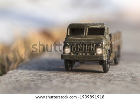 Toy military vehicle on asphalt with blurred background