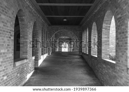 Long Hallway with Light coming Through Arch Brick Windows in black and white. Royalty-Free Stock Photo #1939897366