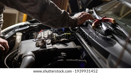 Hands of car mechanic. Protective gloves and tools. Auto service. Car repairing and maintenance. Royalty-Free Stock Photo #1939931452