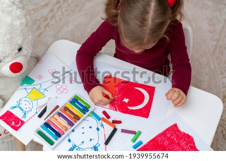 Portrait of small baby girl painting at home. Cute little child drawing Turkish flag picture. Turkish National Sovereignty and Children's Day or Commemoration of Atatürk Youth and Sports Day concept.