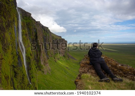 photographer lying down at the edge of a cliff near waterfall hoping for a good shot taking picture with his camera with big lense