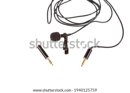 Small lavalier microphone or lapel mic with clip and adapter for computer on white background. Professional sound recording equipment for cell phone.