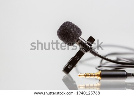 Small lavalier microphone or lapel mic with clip on white background. Professional sound recording equipment for cell phone.