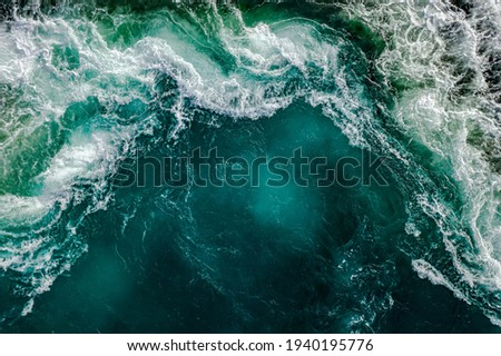 Waves of water of the river and the sea meet each other during high tide and low tide. Whirlpools of the maelstrom of Saltstraumen, Nordland, Norway Royalty-Free Stock Photo #1940195776