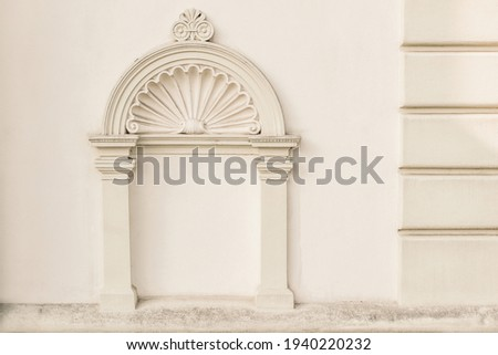 Decorative arch and semi vault above niche with classic pillars. Architectural stucco detail of old European buildingin Prague. Elegant masonry facade decor in beige color. No people, front view. Royalty-Free Stock Photo #1940220232