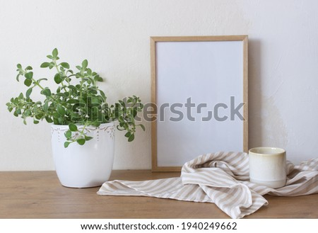 Spring still life. Blank wooden picture frame mockup on wooden table, Medicinal herb Plectranthus amboinicus, and tea. Common names in English include Indian borage, country borage, French thyme.