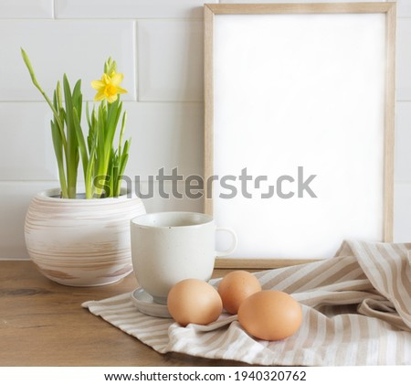 Spring, Easter breakfast still life. A cup of milk, narcissus, daffodil flowers, hen eggs, and empty picture frame mockups. Linen tablecloth. Farmhouse, Scandinavian interior.