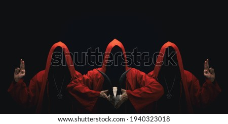 Mystery people in a red hooded cloaks in the dark. Hiding face in shadow. Pointing up with fingers. Satanic symbols. Ghostly figure. Royalty-Free Stock Photo #1940323018