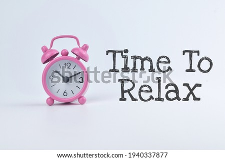 Selective focus image of clock with pink colour with Time To Relax wording isolated on white background. Conceptual image.