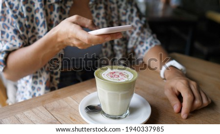 Blogger taking a picture of green tea matcha latte decorated with flowers. Healthy organic plant based drinks