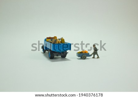 View of a miniature figure scene. A blue truck stands fully loaded with luggage while a worker pushes a handcart with other luggage to the truck. White background. Loading and transportation concept Royalty-Free Stock Photo #1940376178