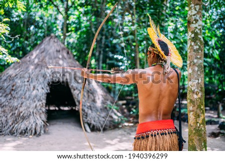 Indian from the Pataxó tribe using a bow and arrow. Brazilian Indian with feather headdress and necklace Royalty-Free Stock Photo #1940396299