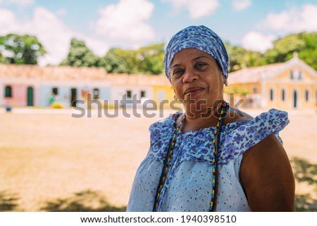 Happy Brazilian woman dressed in the traditional Bahian costume of the Umbanda religion, in the historic center of Porto Seguro Royalty-Free Stock Photo #1940398510