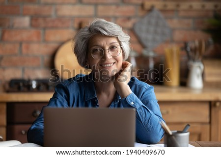 Headshot portrait of happy senior aged hispanic female sit at desk use laptop work study distantly. Confident old age woman remote worker freelancer look at camera at home office workplace at kitchen