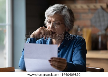 Ugly news. Distressed old age hispanic female check documents at home office read debt bankruptcy information in financial report. Upset stressed older latin woman get bad surprise in official letter Royalty-Free Stock Photo #1940409892