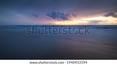 Baltic sea at sunset. Dramatic twilight sky, blue and pink glowing clouds, golden sunlight. Waves, splashing water. Picturesque scenery, seascape, cloudscape, nature. Panoramic view, long exposure Royalty-Free Stock Photo #1940433394