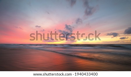 Baltic sea at sunset. Dramatic twilight sky, blue and pink glowing clouds, golden sunlight. Waves, splashing water. Picturesque scenery, seascape, cloudscape, nature. Panoramic view, long exposure Royalty-Free Stock Photo #1940433400