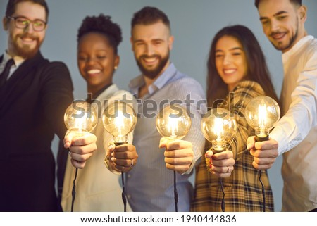 Happy creative team holding glowing lit lightbulbs. Diverse collaboration group of intelligent young multicultural business people with shining light bulbs presenting and sharing effective useful idea Royalty-Free Stock Photo #1940444836