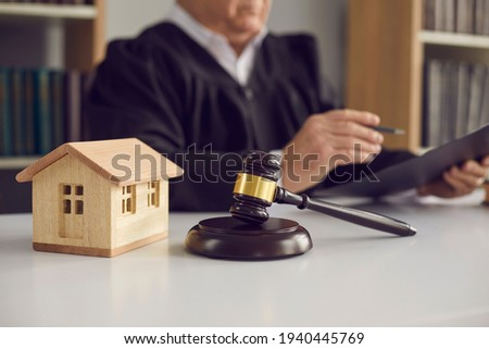 Close-up of judge's gavel, sound block, and small wooden toy house on courtroom table in court. Concept of real estate law, partition of property, separation of estates and divorce settlement
