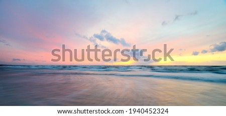Baltic sea at sunset. Dramatic sky, blue and pink glowing clouds, soft golden sunlight. Waves, splashing water. Picturesque dreamlike seascape, cloudscape, nature. Panoramic view, long exposure Royalty-Free Stock Photo #1940452324