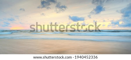 Baltic sea at sunset. Dramatic sky, blue and pink glowing clouds, soft golden sunlight. Waves, splashing water. Picturesque dreamlike seascape, cloudscape, nature. Panoramic view, long exposure Royalty-Free Stock Photo #1940452336
