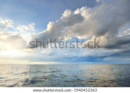 Baltic sea shore after the storm. Dramatic sunset sky, glowing clouds, golden sunlight. Waves, splashing water. Picturesque panoramic scenery, seascape, cloudscape. Nature, environment, ecology Royalty-Free Stock Photo #1940452363