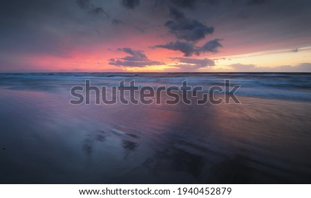 Baltic sea at sunset. Dramatic twilight sky, blue and pink glowing clouds, golden sunlight. Waves, splashing water. Picturesque scenery, seascape, cloudscape, nature. Panoramic view, long exposure Royalty-Free Stock Photo #1940452879