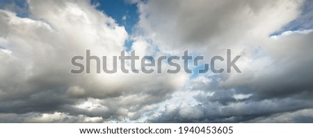 Epic storm cloudscape. White ornamental sunset cumulus clouds. Soft sunlight, sun rays. Clear blue sky. Natural pattern, texture, background, wallpaper, 3D, graphic resources, design, copy space Royalty-Free Stock Photo #1940453605