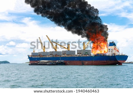 Large general cargo ship for logistic import export goods and other the explosion and had a lot of fire and smoke at sea in bright day Royalty-Free Stock Photo #1940460463