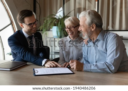 Excited senior couple buyers sign paper contract buy house or apartment from smiling male realtor or broker. Happy mature man and woman spouses make deal put signature on agreement. Rent concept.