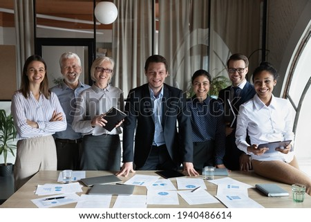 Portrait of happy multiracial businesspeople stand pose at workplace in modern office. Smiling diverse multiethnic employees colleagues show leadership unity. Success, employment concept. Royalty-Free Stock Photo #1940486614