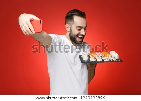 Excited young bearded man 20s in white t-shirt doing selfie shot on mobile phone hold makizushi sushi roll served on black plate traditional japanese food isolated on red background studio portrait